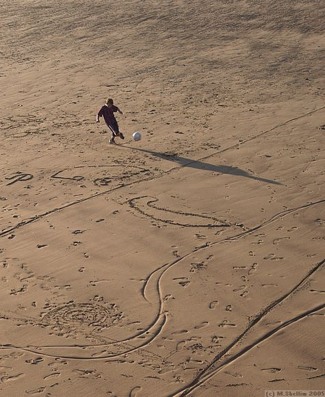 Kid playing football in the sand